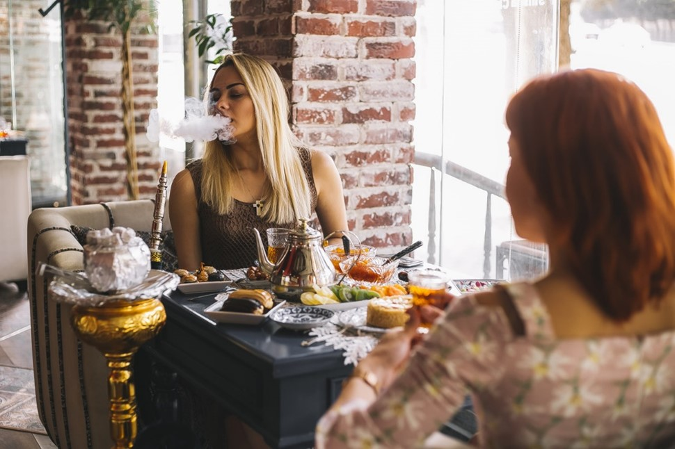 Una mujer en frente de comida  Descripción generada automáticamente con confianza media